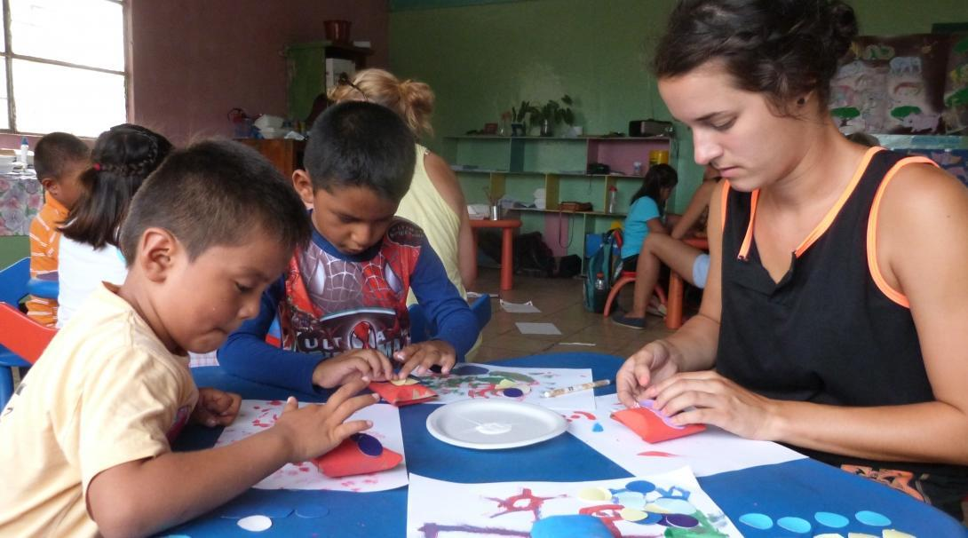 Female Projects Abroad volunteer with children in Ecuador is doing crafts during Childcare Project.